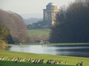 view over lake geese and mausoleum at castle howard yorkshire