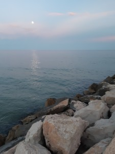 full moon in a dusk sky that reflects over the sea by the rocks of cambrils on the coast of catalonia