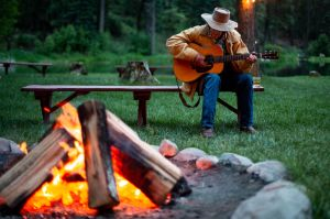 man playing a guitar by the campfire at californias greenhorn ranch