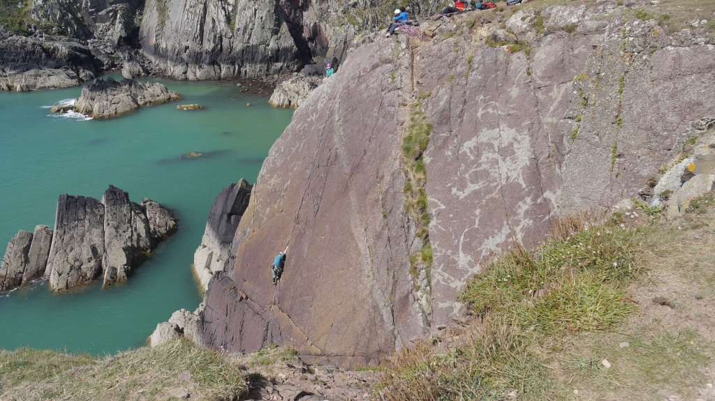 people climbing down a cliff in wales